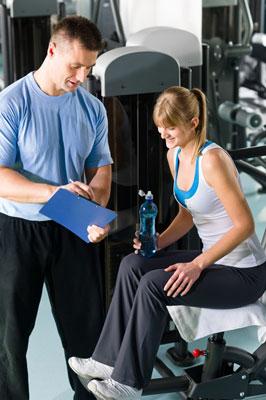 frau im fitnesscenter mit personal trainer